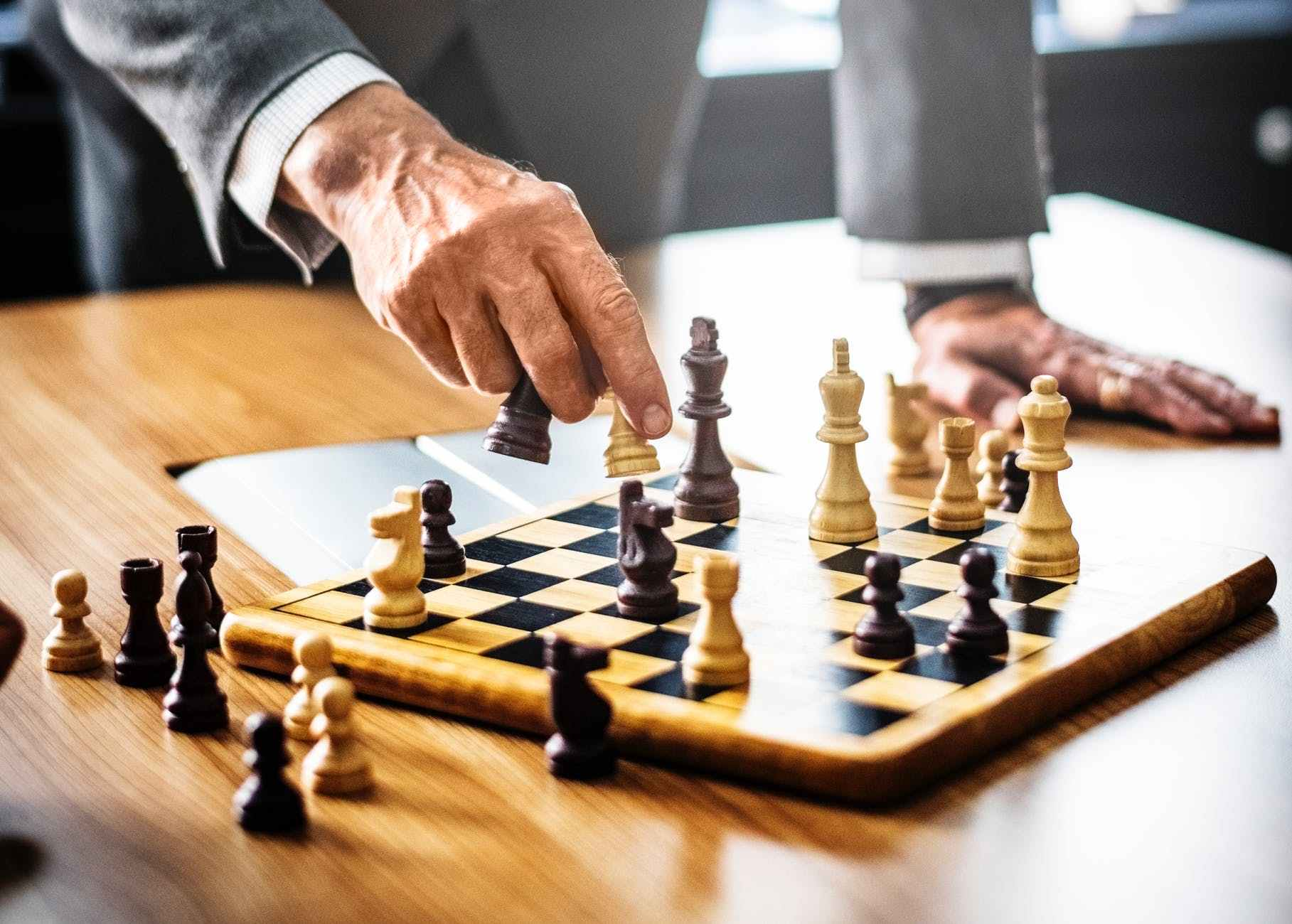 man in gray suit playing chess